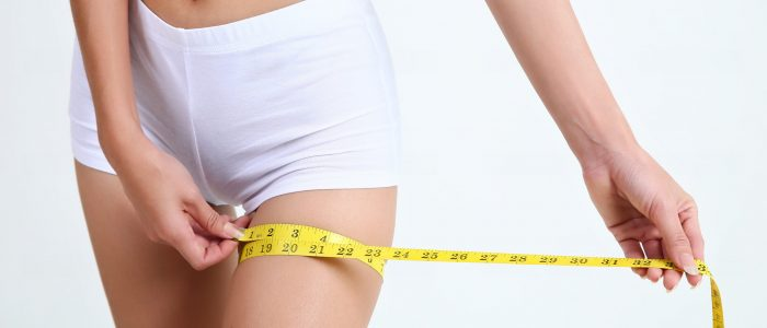 Close up young woman measuring thigh and leg size with tape isolated on white background and copy space, healthy concept.